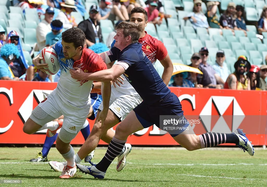 Martin Laveau of France (L) fights off a tackle by James Johnstone of Scotland (R) to score a try during their Bowl quarter-final game at the Sydney Sevens rugby union tournament in Sydney on February 7, 2016. AFP PHOTO / Peter PARKS PARKS