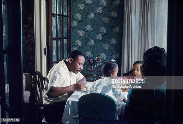 Martin Luther King Jr and his family eat their Sunday dinner after church A woman brings more food to the table