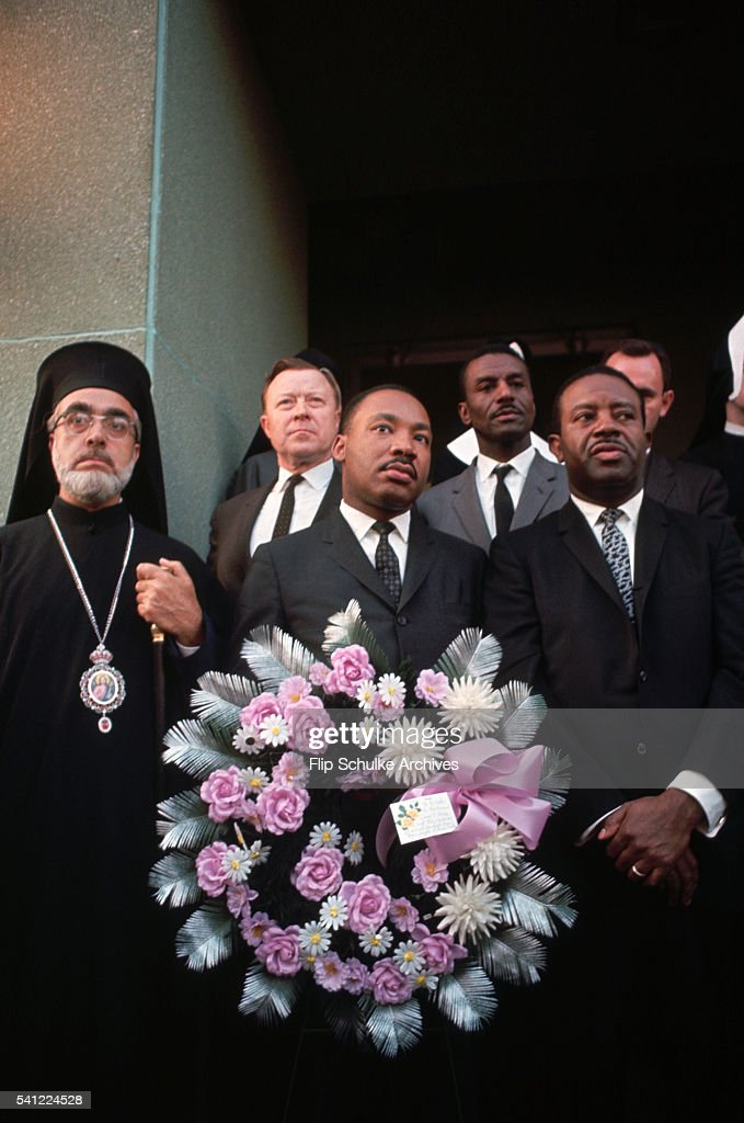 Martin Luther King Jr. holds a wreath as he attends a memorial service for Reverend Jim Reeb with other clergymen. Reeb, a Unitarian minister was killed by segregationists while participating in the marches from Selma to Montgomery. The service was held on the steps of the Dallas County Court House in Selma.