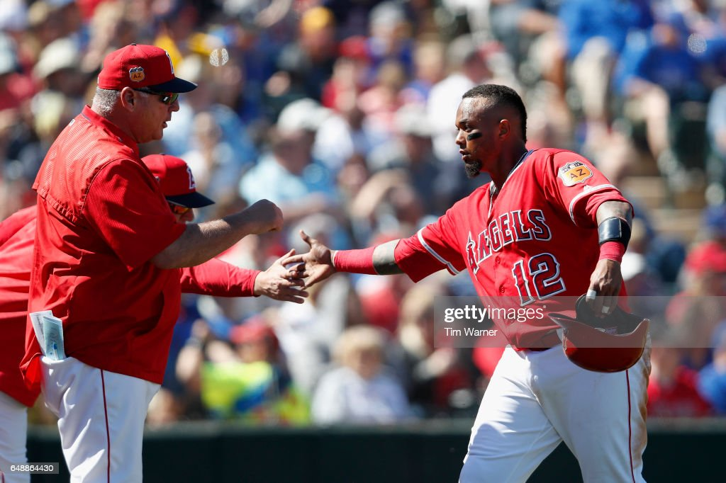 Martin Maldonado #12 of the Los Angeles Angels is greeted by Mike Scioscia #14 of the Los Angeles Angels after a scoring in the second inning during the spring training game at Tempe Diablo Stadium on March 6, 2017 in Tempe, Arizona.