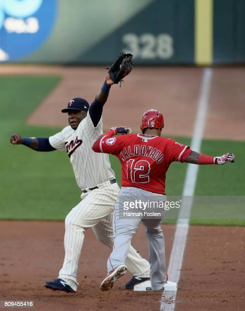 Martin Maldonado of the Los Angeles Angels of Anaheim is out at first base as Miguel Sano of the Minnesota Twins fields the ball during the second...