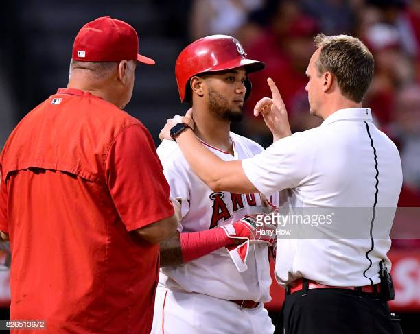 Martin Maldonado of the Los Angeles Angels receives an evaluation after he was hit in the helmet by a pitch during the second inning against the...