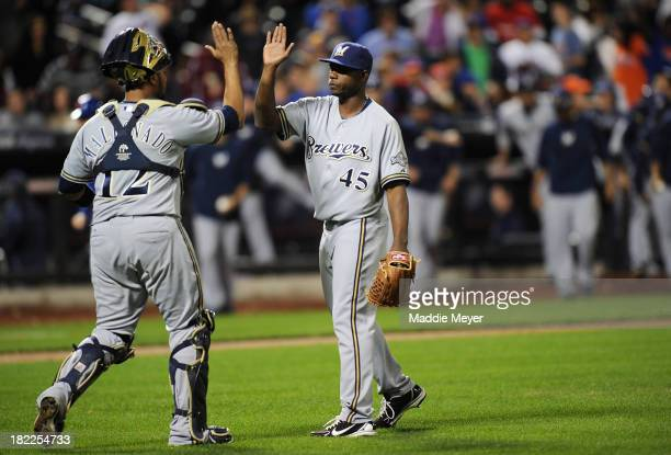 Martin Maldonado of the Milwaukee Brewers and Alfredo Figaro celebrate following the game against the New York Mets at Citi Field on September 28...