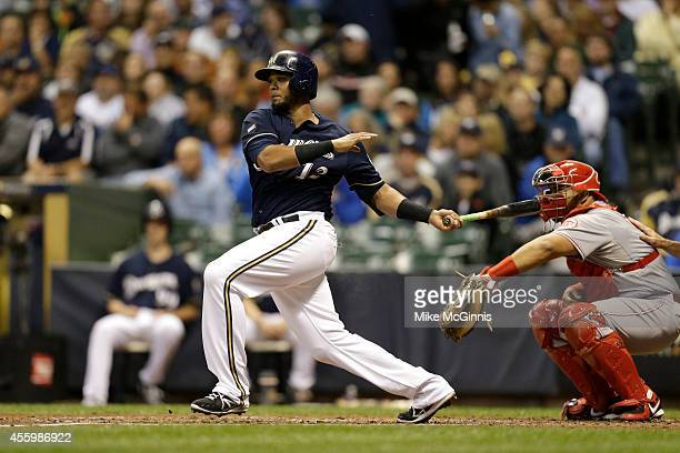 Martin Maldonado of the Milwaukee Brewers makes some contact at the plate during the game against the Cincinnati Reds at Miller Park on September 12...