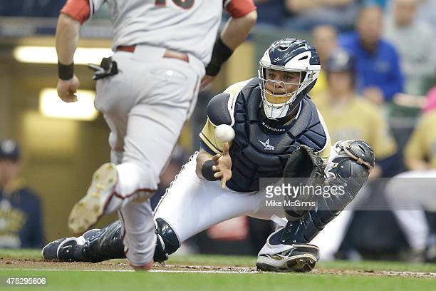 Martin Maldonado of the Milwaukee Brewers misses the ball at home plate allowing Chris Owings of the Arizona Diamondbacks to score during the second...