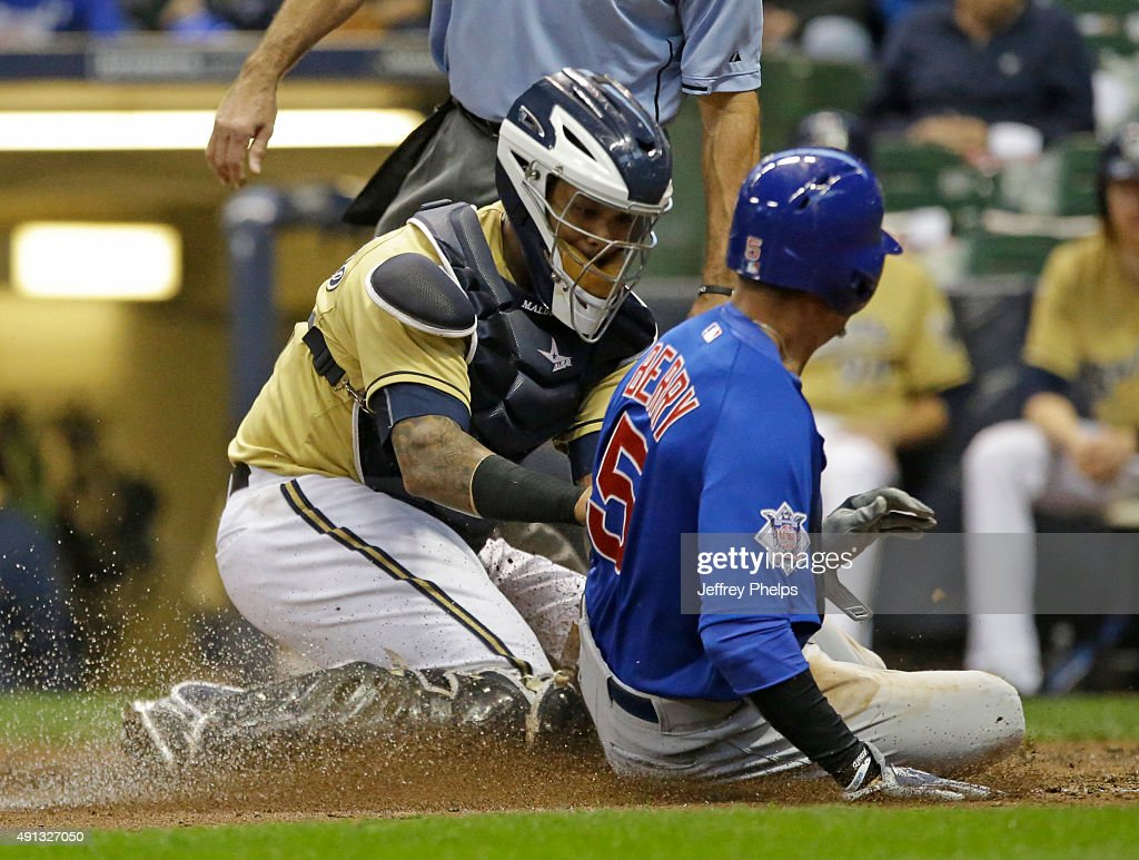 Martin Maldonado of the Milwaukee Brewers tags out Quintin Berry of the Chicago Cubs at home plate in the eighth inning of a baseball game at Miller...