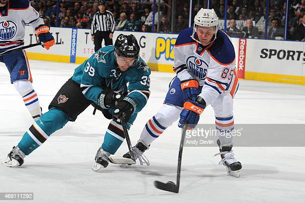 Martin Marincin of the Edmonton Oilers and Logan Couture of the San Jose Sharks battle for the puck during the game on April 9 2015 at Rexall Place...