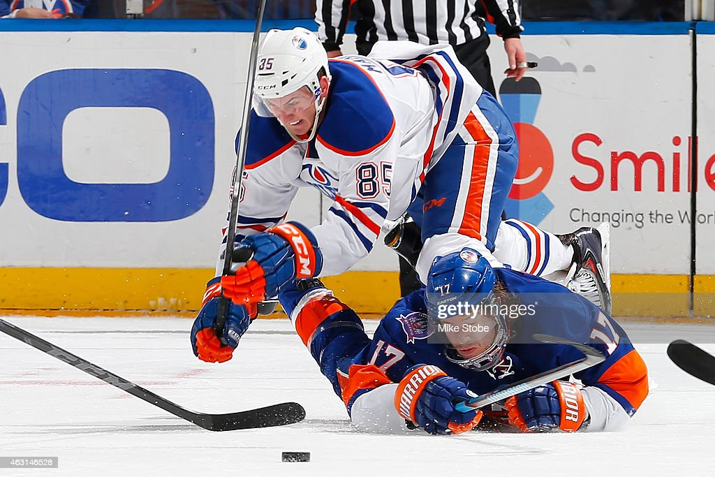Martin Marincin #85 of the Edmonton Oilers and Matt Martin #17 of the New York Islanders battle for the puck at Nassau Veterans Memorial Coliseum on February 10, 2015 in Uniondale, New York.