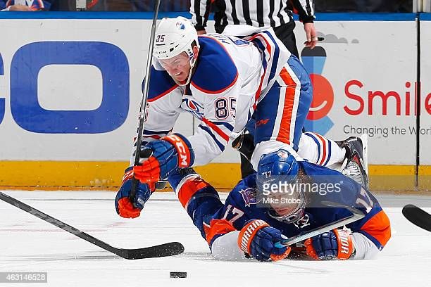 Martin Marincin of the Edmonton Oilers and Matt Martin of the New York Islanders battle for the puck at Nassau Veterans Memorial Coliseum on February...
