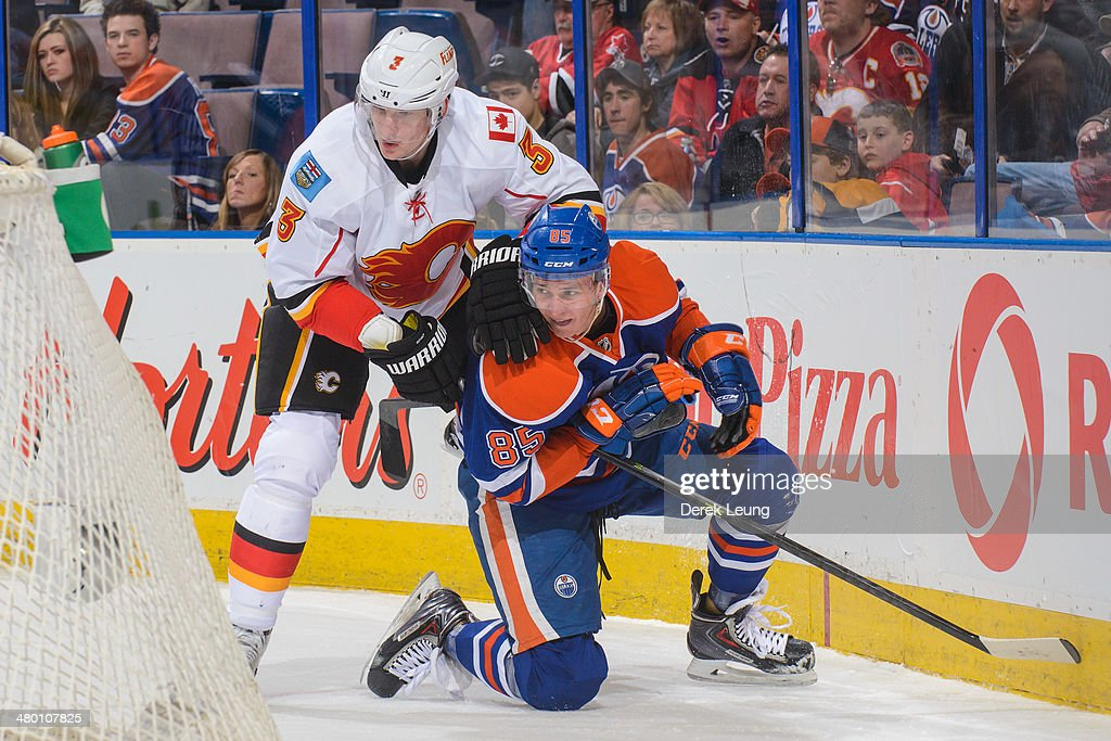 Martin Marincin #85 of the Edmonton Oilers is checked by Ladislav Smid #3 of the Calgary Flames during an NHL game at Rexall Place on March 22, 2014 in Edmonton, Alberta, Canada. The Flames defeated the Oilers 8-1.