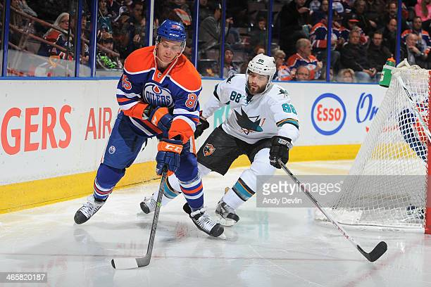 Martin Marincin of the Edmonton Oilers skates with the puck while being pursued by Brent Burns of the San Jose Sharks on January 29 2014 at Rexall...