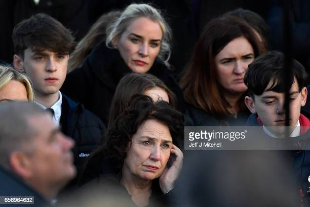 Martin McGuinness's wife Bernadette and other family members stand at the graveside at Martin McGuinness' Funeral at the Derry City Cemetery on March...