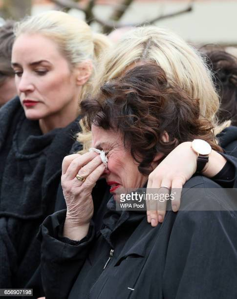 Martin McGuinness's wife Bernadette is comforted ahead of the funeral of former Northern Ireland Deputy First Minister Martin McGuinness outside his...