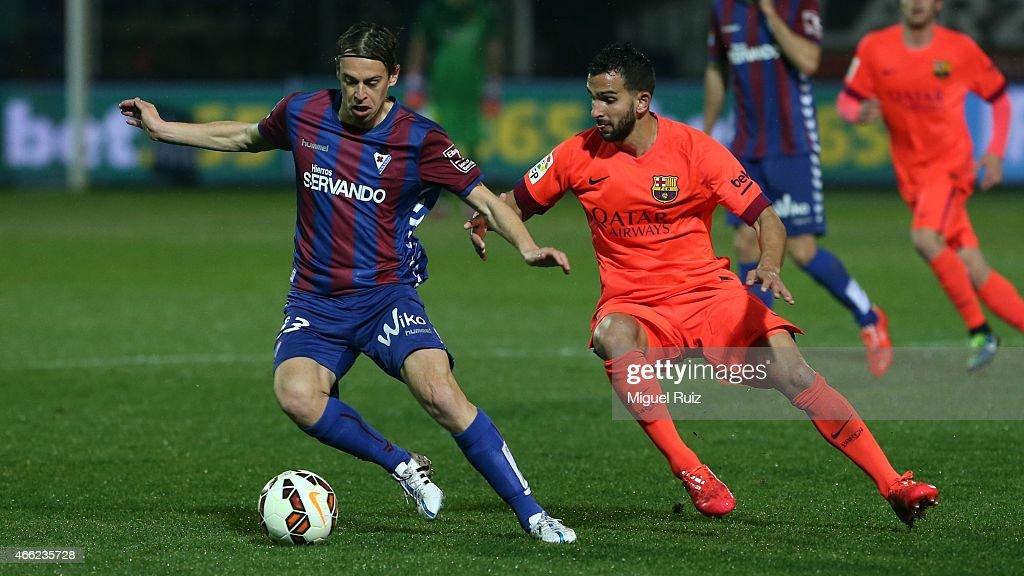 Martin Montoya of FC Barcelona competes for the ball with Javi Lara of SD Eibar during the La Liga match between SD Eibar and FC Barcelona at Ipurua Municipal Stadium on March 14, 2015 in Eibar, Spain.