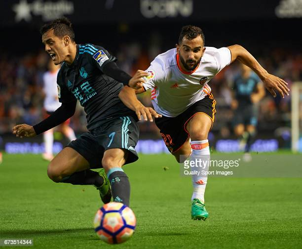 Martin Montoya of Valencia competes for the ball with Juanmi Jimenez of Real Sociedad during the La Liga match between Valencia CF and Real Sociedad...