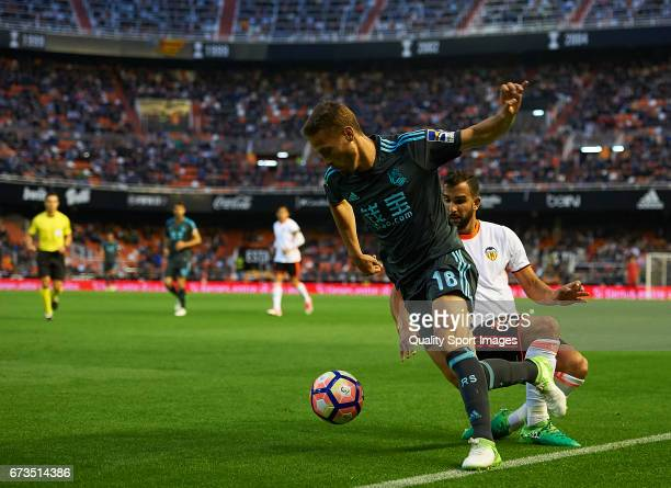 Martin Montoya of Valencia competes for the ball with Sergio Canales of Real Sociedad during the La Liga match between Valencia CF and Real Sociedad...