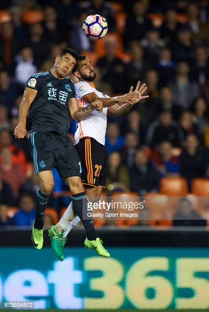 Martin Montoya of Valencia competes for the ball with Yuri Berchiche Izeta of Real Sociedad during the La Liga match between Valencia CF and Real...