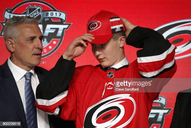 Martin Necas 12th overall pick of the Carolina Hurricanes puts on his hat onstage during Round One of the 2017 NHL Draft at United Center on June 23...