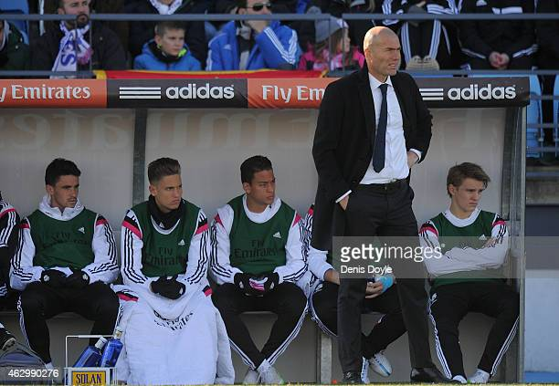 Martin Odegaard of Real Madrid Castilla looks on from the substitutes bench beside head coach Zinedine Zidane during the Segunda Division B match...