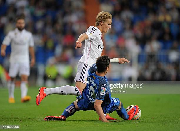 Martin Odegaard of Real Madridis tackled by Sergio Escudero of Getafe CF during the La Liga match between Real Madrid CF and Getafe CF at Estadio...