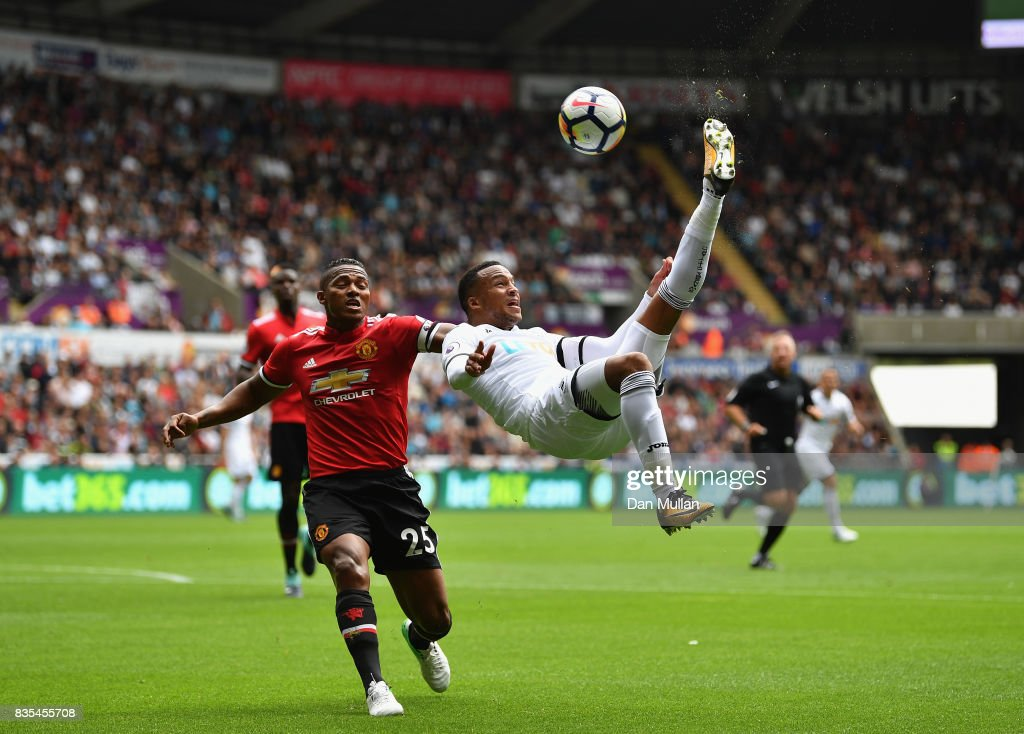 Martin Olsson of Swansea City attempts a over head kick as Antonio Valencia of Manchester Uited puts pressure on him during the Premier League match between Swansea City and Manchester United at Liberty Stadium on August 19, 2017 in Swansea, Wales.