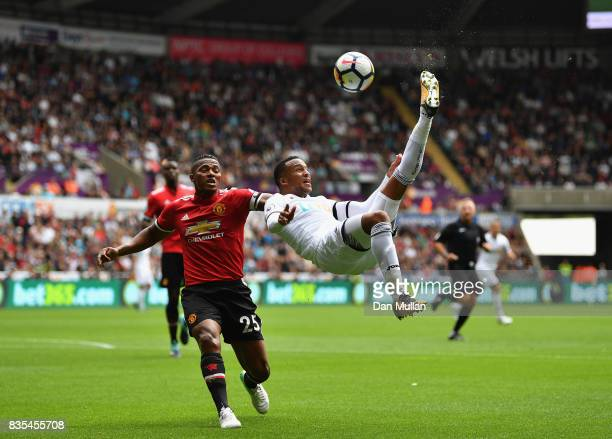 Martin Olsson of Swansea City attempts a over head kick as Antonio Valencia of Manchester Uited puts pressure on him during the Premier League match...