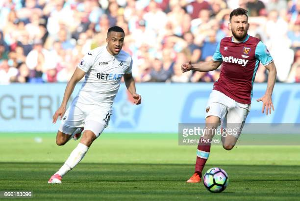 Martin Olsson of Swansea City is closely marked by Robert Snodgrass of West Ham United during the Premier League match between West Ham United and...