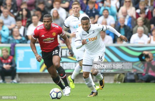 Martin Olsson of Swansea City is marked by Antonio Valencia of Manchester United during the Premier League match between Swansea City and Manchester...