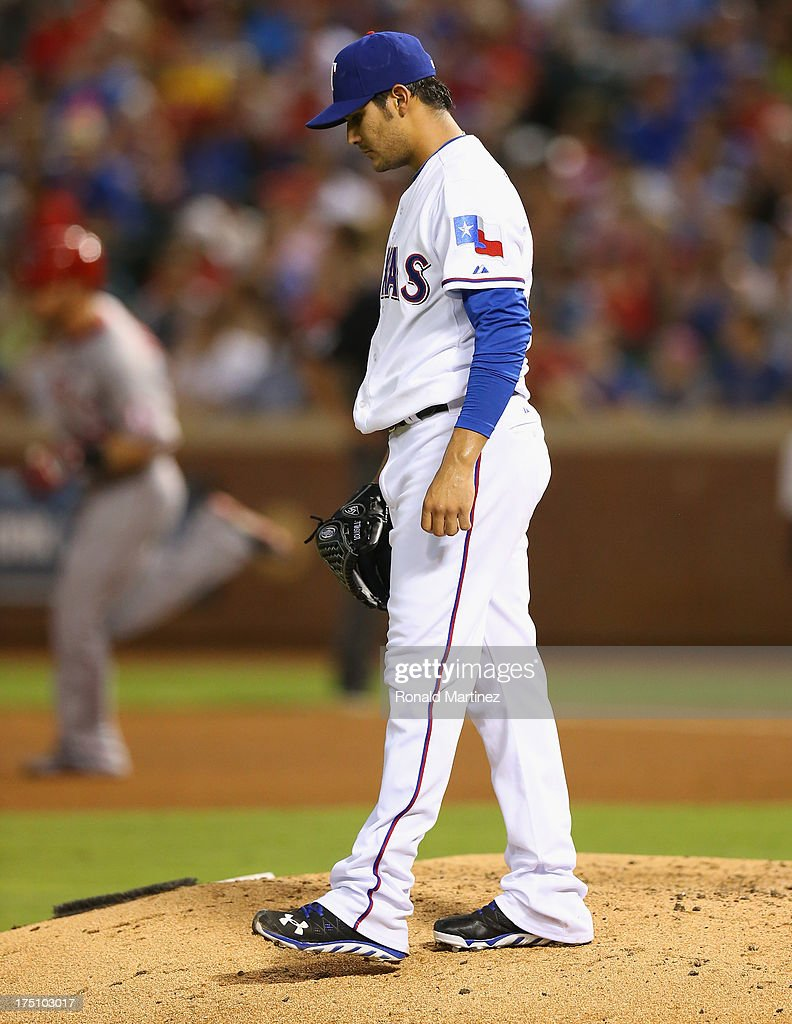 Martin Perez #33 of the Texas Rangers steps off the mound after giving up a homerun against Josh Hamilton #32 of the Los Angeles Angels at Rangers Ballpark in Arlington on July 31, 2013 in Arlington, Texas.