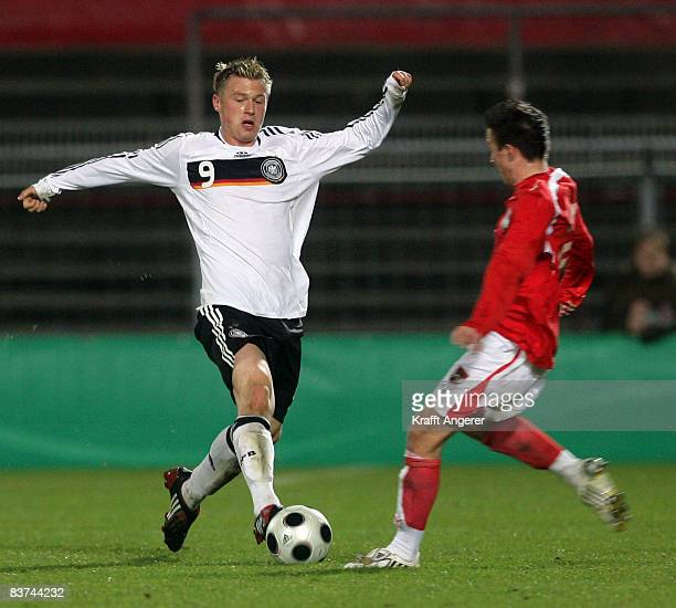 Martin Pourie of Germany challenges for the ball with Daniel Schuetz of Austria during the Men's U18 international friendly match between Germany and...