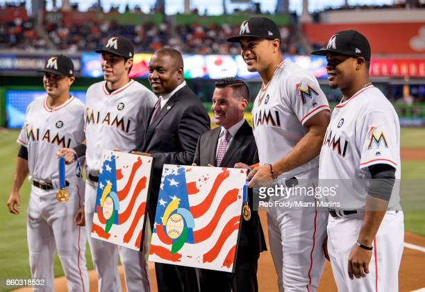 Martin Prado Christian Yelich Giancarlo Stanton and Edinson Volquez of the Miami Marlins are honored by Michael Hill and David Sampson for...