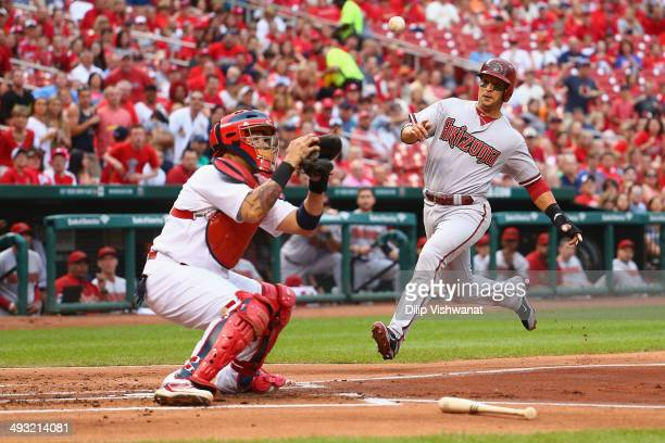 Martin Prado of the Arizona Diamondbacks beats the throw to Yadier Molina of the St Louis Cardinals to score a run in the first inning at Busch...