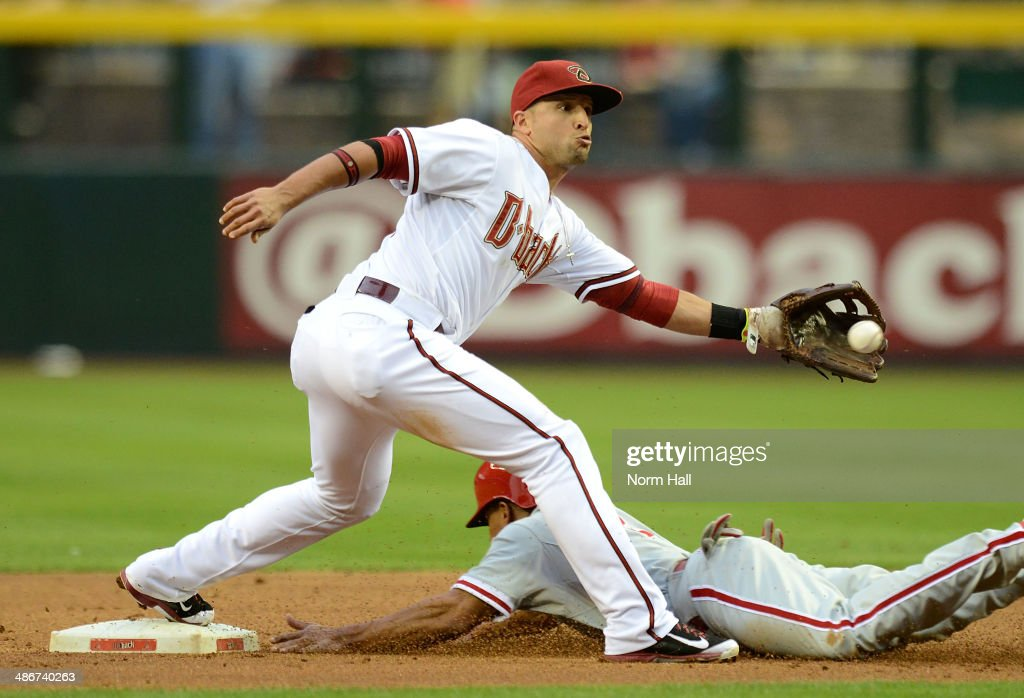 Martin Prado #14 of the Arizona Diamondbacks catches a throw while covering second base as Ben Revere #2 of the Philadelphia Phillies slides safely into the bag during the first inning at Chase Field on April 25, 2014 in Phoenix, Arizona.