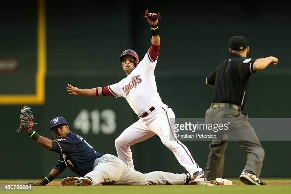 Martin Prado of the Arizona Diamondbacks is called out at second base after a force out by infielder Jean Segura of the Milwaukee Brewers during the...