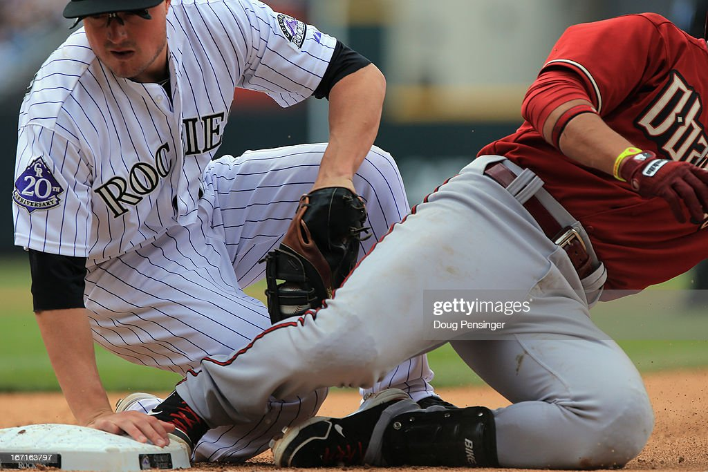 Martin Prado #14 of the Arizona Diamondbacks slides safely back to first base ahead of the tag by first baseman Jordan Pacheco #15 of the Colorado Rockies at Coors Field on April 21, 2013 in Denver, Colorado. The Diamondbacks defeated the Rockies 5-4.