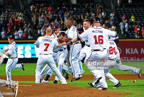 Martin Prado of the Atlanta Braves is mobbed by teammates after knocking in the gamewinning run in the 11th inning against the San Francisco Giants...
