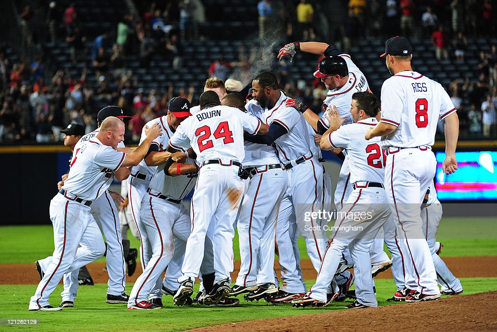 <a gi-track='captionPersonalityLinkClicked' href=/galleries/search?phrase=Martin+Prado&family=editorial&specificpeople=620159 ng-click='$event.stopPropagation()'>Martin Prado</a> #14 of the Atlanta Braves is mobbed by teammates after knocking in the game-winning run in the 11th inning against the San Francisco Giants at Turner Field on August 16, 2011 in Atlanta, Georgia.