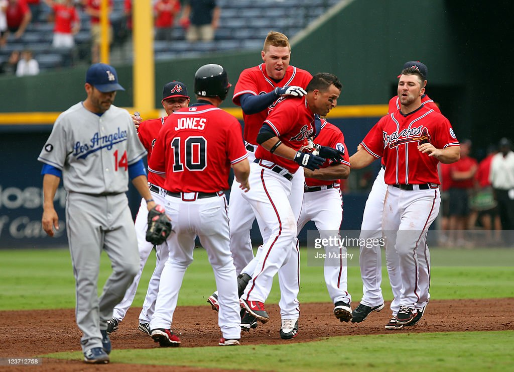 Martin Prado #14 of the Atlanta Braves is mobbed by teammates Chipper Jones #10, Freddie Freeman #5 and Dan Uggla #26 of the Atlanta Braves after hitting a walk-off single as Jamey Carroll #14 of the Los Angeles Dodgers walks off the field on September 4, 2011 at Turner Field in Atlanta, Georgia.