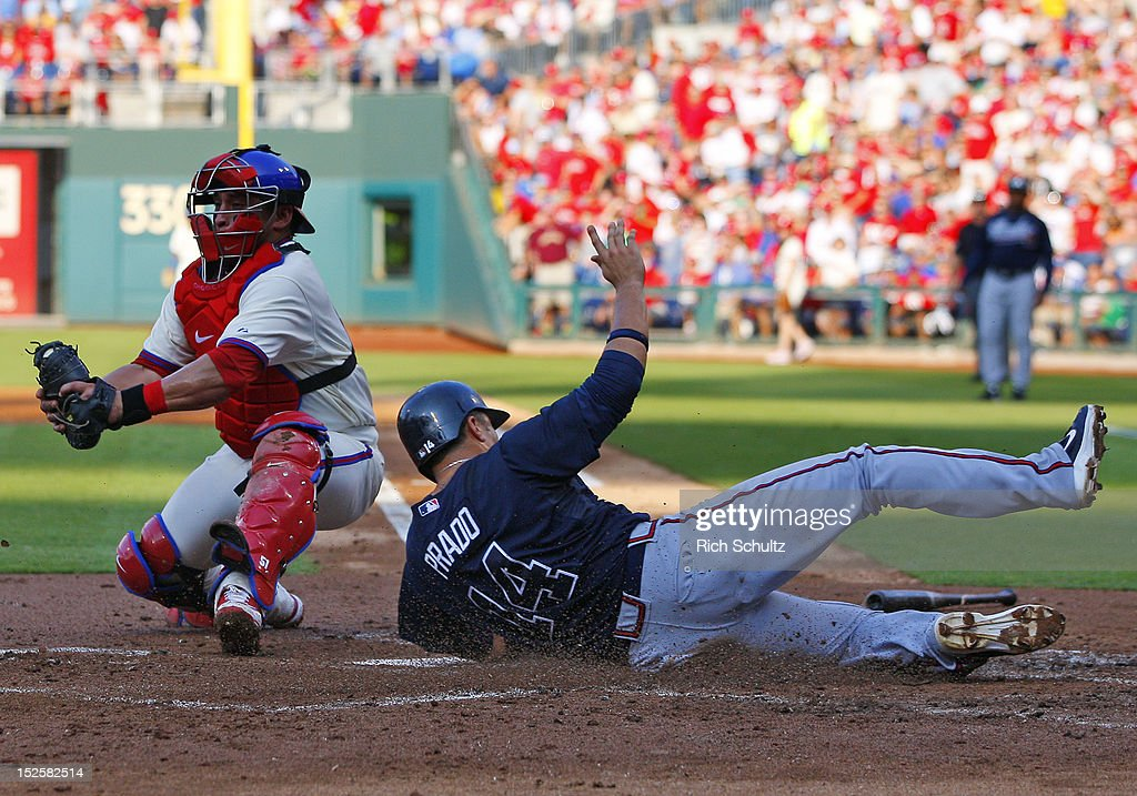 Martin Prado #14 of the Atlanta Braves scores on a single by Jason Heyward #22 before catcher Carlos Ruiz #51 can make the tag during the second inning in a MLB baseball game on September 22, 2012 at Citizens Bank Park in Philadelphia, Pennsylvania.