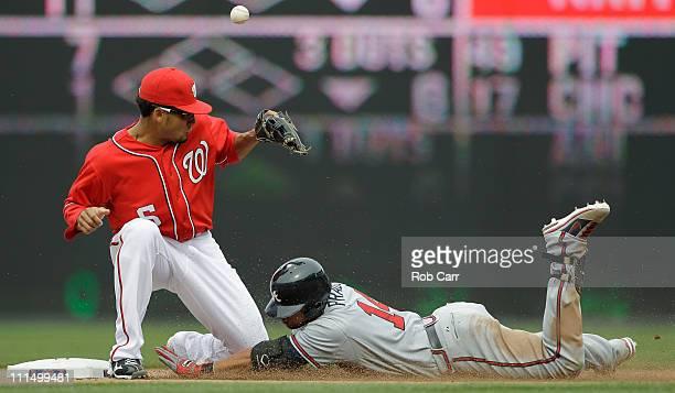 Martin Prado of the Atlanta Braves slides safely into second base for a double as shortstop Ian Desmond of the Washington Nationals bobbles the throw...