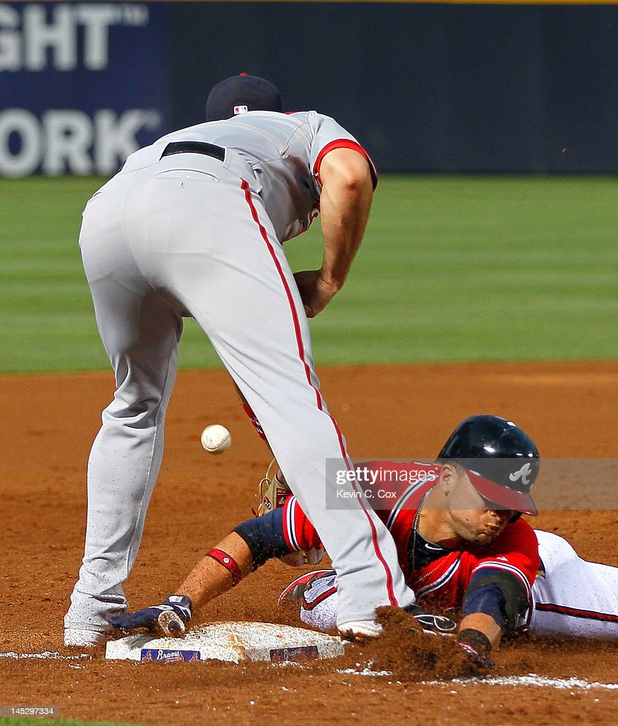 <a gi-track='captionPersonalityLinkClicked' href=/galleries/search?phrase=Martin+Prado&family=editorial&specificpeople=620159 ng-click='$event.stopPropagation()'>Martin Prado</a> #14 of the Atlanta Braves slides safely into third base under <a gi-track='captionPersonalityLinkClicked' href=/galleries/search?phrase=Ryan+Zimmerman+-+Baseball+Player&family=editorial&specificpeople=534809 ng-click='$event.stopPropagation()'>Ryan Zimmerman</a> #11 of the Washington Nationals in the third inning at Turner Field on May 25, 2012 in Atlanta, Georgia.