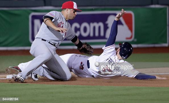 Martin Prado of the Miami Marlins misses a tag at third base on Freddie Freeman of the Atlanta Braves during their game at Fort Bragg Field on July 3...