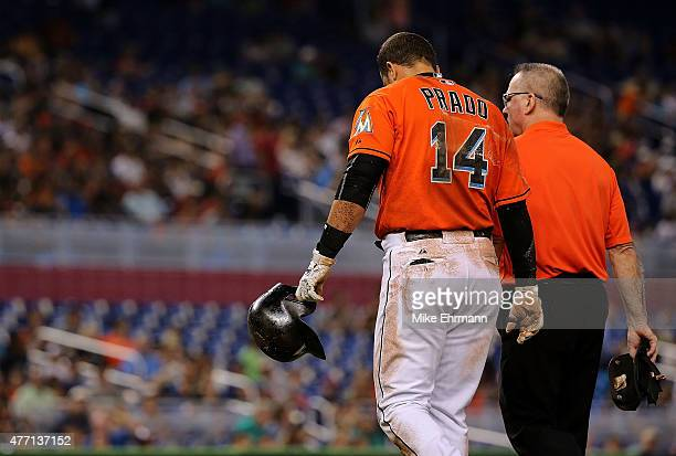 Martin Prado of the Miami Marlins reacts to injuring his shoulder after falling crossing first base during a game against the Colorado Rockies at...