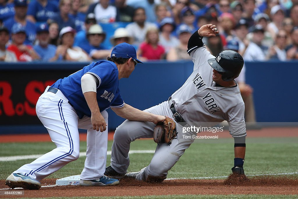 Martin Prado #14 of the New York Yankees slides safely into third base in the fourth inning during MLB game action as Danny Valencia #15 of the Toronto Blue Jays applies the late tag on August 31, 2014 at Rogers Centre in Toronto, Ontario, Canada.