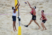 Martin Reader of Canada jumps at the net with Ricardo Santos of Brazil during the Men's Beach Volleyball preliminary match between the Brazil and...