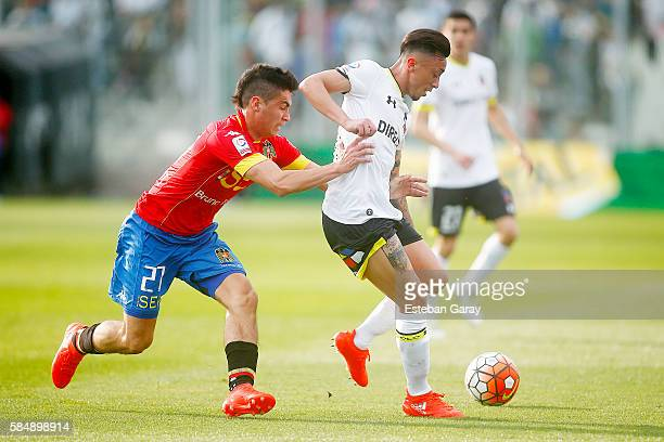 Martin Rodriguez of Colo Colo fights for the ball with Pablo Galdames of Union Espanola during a match between Colo Colo and Union Española as part...