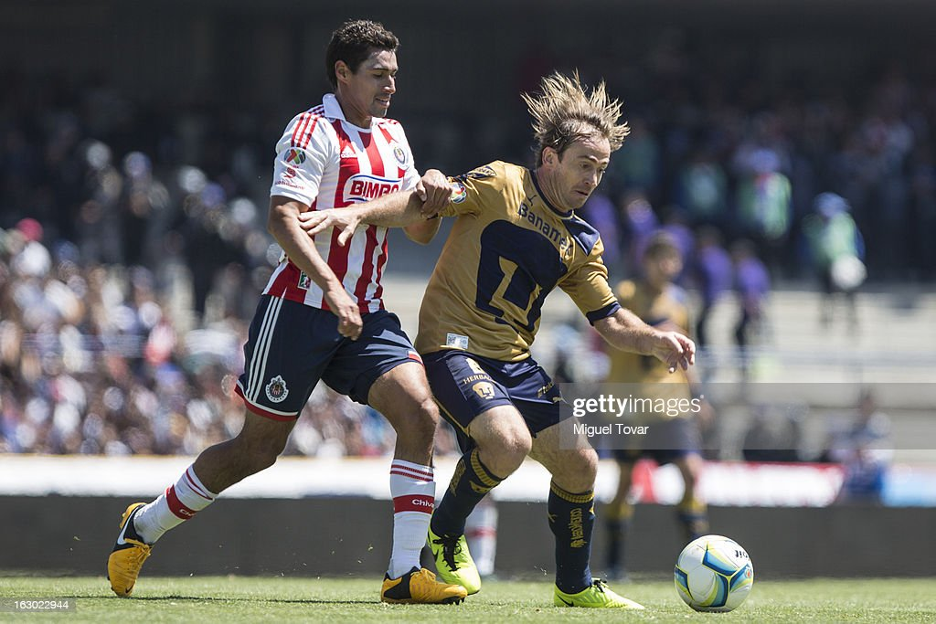 Martin Romagnoli (R) of Pumas struggles for the ball with Patricio Araujo (L) of Chivas during a match between Pumas and Chivas as part of Clausura 2013 Liga MX at Olympic Stadium on March 03, 2013 in Mexico City, Mexico.