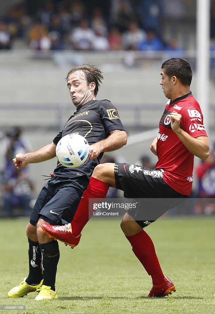 Martin Romagnoli of Pumas UNAM figths for the ball with Henry Martin of Xolos of Tijuana during a match between Pumas UNAM and Xolos Tijuana as part of 6th round Apertura 2014 Liga MX at Olimpic Stadium on August 24, 2014 in Mexico City, Mexico.