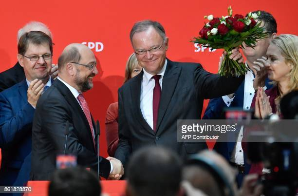 Martin Schulz leader of Germany's social democratatic SPD party congratulates Lower Saxony's State Premier Stephan Weil who is waving a bouquet on...