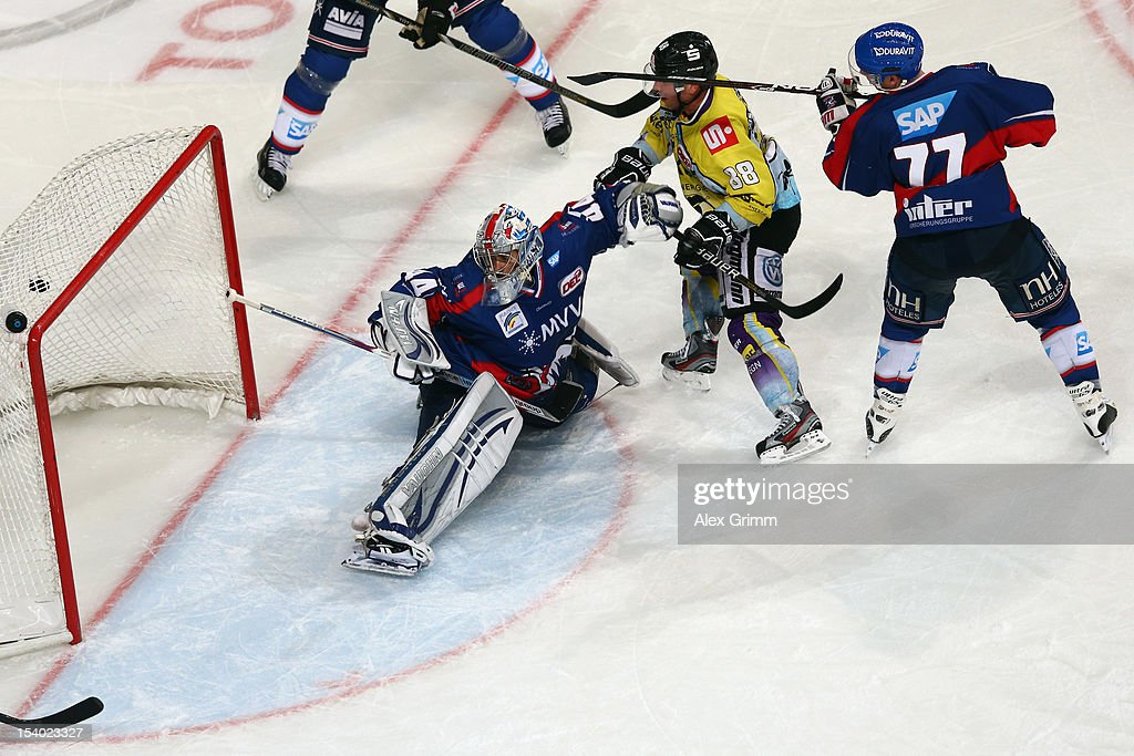 Martin Schymainski of Krefeld scores his team's fifth goal against Nikolai Goc and goalkeeper <a gi-track='captionPersonalityLinkClicked' href=/galleries/search?phrase=Dennis+Endras&family=editorial&specificpeople=5526366 ng-click='$event.stopPropagation()'>Dennis Endras</a> of Mannheim during the DEL match between Adler Mannheim and Krefeld Pinguine at SAP-Arena on October 12, 2012 in Mannheim, Germany.